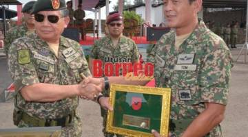 TERIMALAH: Ahmad Hasbullah (kiri) menyerahkan plak bendera 13 Briged kepada Panglima 13 Briged Brigadier Jeneral Datuk Arman Rumaizi Ahmad semasa penstrukturan semula 13 Briged baru-baru ini.