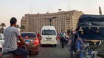 TEGAS: Seorang anggota polis menahan trafik yang melalui bulatan di Dataran Tahrir, tengah Kaherah kelmarin. — Gambar AFP