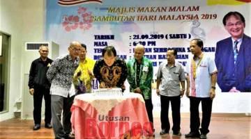 RAIKAN BERSAMA: Baru (empat kanan) serta yang lain ketika meraikan Majlis Makan Malam Sambutan Hari Malaysia di Selangau, kelmarin.