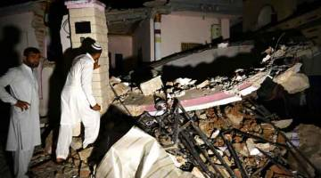 RUNTUH: Penduduk meninjau bangunan yang runtuh selepas gempa bumi cetek melanda           berhampiran kota Mirpur di timur laut Pakistan kelmarin. — Gambar AFP     Pakistani men stand beside a collapsed building following an earthquake on the outskirts of Mirpur on September 24, 2019. - At least 19 people have been killed and 300 wounded after a shallow earthquake rattled north-eastern Pakistan, a senior police officer said, with the tremor tearing car-sized cracks into roads and heavily damaging infrastruc
