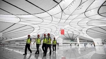 FUTURISTIK: Gambar fail diambil pada 25 Jun lepas menunjukkan sekumpulan pekerja berjalan menerusi bangunan terminal                   di Lapangan Terbang Antarabangsa Beijing Daxing di Beijing, China yang dibuka secara rasmi bermula semalam. — Gambar AFP
