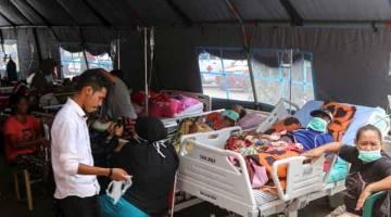 TERIMA RAWATAN: Penduduk yang cedera menerima rawatan di pusat penempatan sementara di luar hospital Dr. M. Haulussy selepas gempa bumi melanda Ambon di Kepulauan Maluku, Indonesia kelmarin. — Gambar Antara Foto/Izaac Mulyawan/Reuters