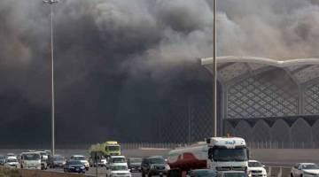 TERBAKAR: Kenderaan bergerak melalui kepulan asap tebal dari stesen kereta api berkelajuan tinggi Haramain di bandar Jeddah barat Arab Saudi kelmarin, selepas api mula merebak di stesen tersebut. — Gambar AFP