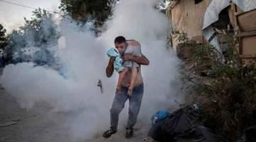 SELAMATKAN DIRI: Seorang lelaki membawa kanak-kanak lelaki semasa petempuran dengan polis di luar kem pelarian Moria di pulau Lesbos Greece, kelmarin. — Gambar AFP