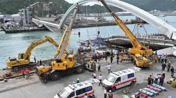 RUNTUH: Anggota penyelamat dilihat bersedia untuk membantu mangsa selepas sebuah jambatan runtuh dan menyebabkan sekurang-kurangnya 14 orang cedera di pelabuhan Nanfangao di pantai timur Taiwan semalam. — Gambar Sam Yeh/AFP