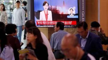TERKINI: Orang ramai menonton berita mengenai misil balistik Korea Utara yang dipercayai              dilancarkan oleh kapal selam, di stesen kereta api di Seoul, Korea Selatan semalam. — Gambar Reuters