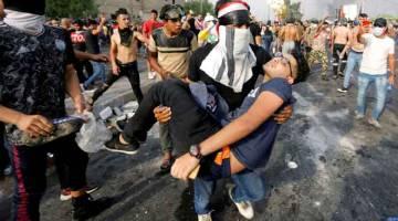 PROTES: Seorang lelaki mengangkat rakannya yang cedera ketika protes untuk mengecam rasuah, perkhidmatan awam yang gagal dan pengangguran di Baghdad, Iraq kelmarin. — Gambar Reuters