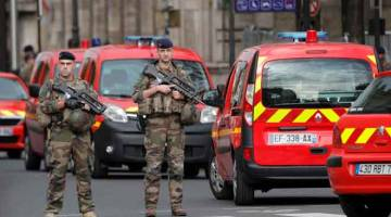 BERKAWAL: Dua anggota tentera dilihat berkawal dekat ibu pejabat polis di Paris kelmarin selepas seorang lelaki bersenjatakan pisau membunuh empat pegawai polis. — Gambar Geoffroy Van Der Hasselt/AFP