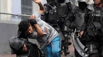 TANGKAP: Polis rusuhan menangkap seorang lelaki semasa pertelingkahan yang meletus selepas kerajaan Moreno memansuhkan subsidi bahan bakar di Quito, Ecuador kelmarin. — Gambar Reuters