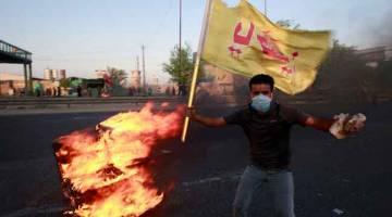 AMARAH: Penunjuk perasaan membakar objek semasa protes antikerajaan bertukar ganas                       di Baghdad, Iraq kelmarin. — Gambar Alaa al-Marjani/Reuters