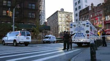 TRAGIK: Anggota polis menjalankan siasatan di tempat kejadian di Manhattan, New York kelmarin. — Gambar Reuters