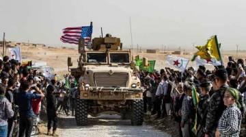 SITUASI BAHARU: Penduduk Kurdis Syria mengerumuni sebuah kereta perisai tentera AS semasa mengadakan demonstrasi mengecam ancaman Turki berdekatan pangkalan tentera pakatan antarabangsa diketuai AS di pinggir bandar Ras al-Ain dalam wilayah Hasakeh dekat sempadan dengan Turki, semalam. — Gambar AFP