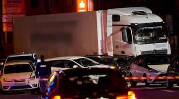 REMUK: Seorang pegawai polis dilihat mengambil gambar sebuah trak curi yang merempuh beberapa kereta di lampu isyarat                  di bandar Limburg, tengah Jerman kelmarin. — Gambar Sascha Ditscher/dpa/AFP