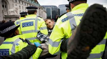 TANGKAP: Pegawai polis menangkap penunjuk perasaan semasa protes 'Extinction Rebellion' di London, Britain kelmarin. — Gambar Reuters