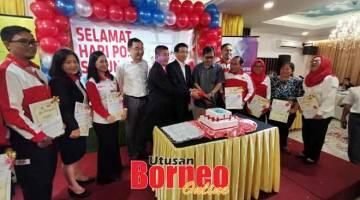 MELAH KEK: Bong (lima kiba), Adiman (tujuh kanan), Abang Sardon (enam kanan) enggau bala staf Pos Malaysia ke bulai deka melah kek dikena ngerami Hari Pos Sedunya 2019 Renggat Sarawak, kemari.