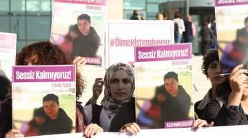 TUNTUT KEADILAN: Sekumpulan wanita memegang plakad dengan gambar Bulut ketika mereka berhimpun di luar mahkamah  di bandar Kirikkale di tengah Anatolia, Turki semalam. — Gambar AFP