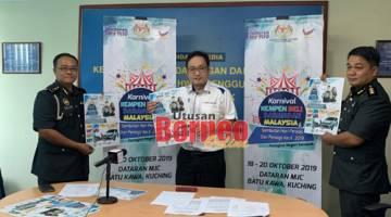 Chong bersama anggota KPDNHEP Sarawak menunjukkan poster Kempen Beli Barangan Malaysia dan Sambutan Hari Penjaja dan Peniaga Kecil Peringkat Negeri Sarawak 2019 pada sidang media di Kuching hari ini
