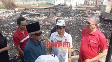 Fadillah (kanan) meninjau tapak rumah-rumah yang musnah dalam kejadian kebakaran di Kampung Sg Bedil di Kuching.