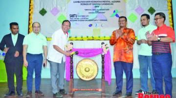 RASMI: Teo (tiga, kiri) memalu gong sebagai simbolik merasmikan Sambutan Hari Kesihatan Mental Sedunia Peringkat Daerah Sandakan.