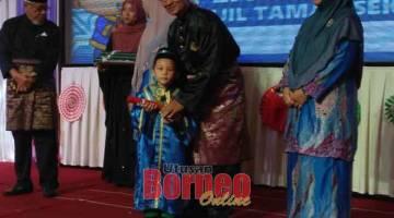 TAHNIAH: Abdul Rahman menyampaikan sijil tamat belajar kepada salah seorang kanak-kanak tadika berkenaan yang akan melangkah ke tahun satu pada 2020.