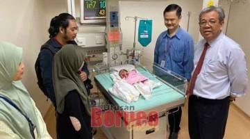 PRIHATIN: Ahmad Johnie (kanan) melawat Aqinnah Sofea, bayi Ahmad Nazren dan Rostina yang mengalami masalah kesihatan usus bocor sejak lahir di Hospital Sungai Buloh, Selangor kelmarin.