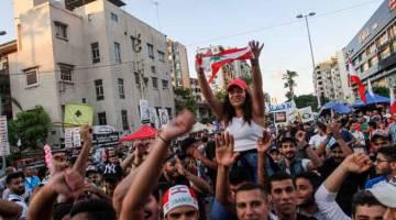 GEMBIRA: Penunjuk perasaan meraikan selepas Hariri (sisipan) mengumumkan peletakan jawatannya pada hari ke-13 protes antikerajaan di kota selatan Sidon, Lubnan kelmarin. — Gambar AFP/Reuters