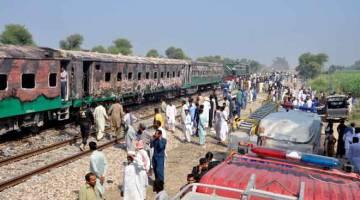 MALANG: Orang ramai melihat gerabak yang hangus sehari selepas sebuah kereta api penumpang terbakar dan mengorbankan 74 nyawa di Rahim Yar Khan, di timur laut Pakistan semalam. — Gambar Arif Ali/AFP