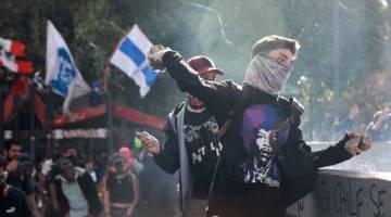 GANAS: Penunjuk perasaan melontar batu ke arah anggota pasukan keselamatan semasa                 demonstrasi antikerajaan di Santiago, Chile kelmarin. — Gambar Henry Romero/Reuters