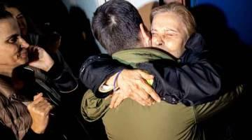 GEMBIRA: Nazli Ilicak disambut dengan pelukan oleh ahli keluarga yang gembira selepas                    pembebasannya dari penjara di Istanbul, Turki kelmarin. — Gambar Yasin Akgul/AFP