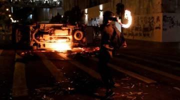 BAKAR: Penunjuk perasaan antikerajaan melontar bom botol ke arah kenderaan yang diterbalikkan semasa protes di daerah Tseung Kwan O, Hong Kong, China kelmarin. — Gambar Tyrone Siu/Reuters