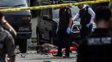 BERKECAI: Anggota polis memeriksa mayat pengebom nekad yang disyaki selepas letupan di pekarangan balai polis di Medan, Pulau Sumatra, Indonesia semalam. — Gambar Albert Damanik/AFP