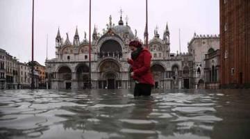 BANJIR: Seorang wanita dilihat meredah banjir di Dataran St Mark selepas air pasang tinggi melanda Venice, Itali semalam. — Gambar Marco Bertorello/AFP