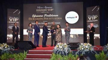 LONJAK SYARIKAT TEMPATAN: Ahmad Luqman (empat kiri) bertukar MoU dengan Wan Suraya disaksikan Menteri Pembangunan Usahawan, Datuk Seri Mohd Redzuan Md Yusof.