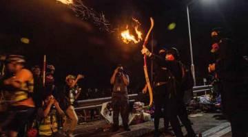 PANAH: Penunjuk perasaan melepaskan panah berapi untuk membakar perintang di Chinese University of Hong Kong (CUHK) di Hong Kong, China kelmarin. — Gambar Anthony Wallace/AFP
