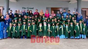 TANDA KENANG: Fatimah (baris belakang, lapan kanan) maya begulai enggau 60 iku nembiak mit ke graduet ari tujuh Palan SeDIDIK Zon Mukah maya konvokesyen nya.