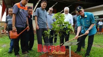 HIJAU: Junaidi (kanan) menanam pokok manggis, sambil disaksikan Abdul Jaafar (tiga kiri) dan yang lain. — Gambar Muhamad Rais Sanusi