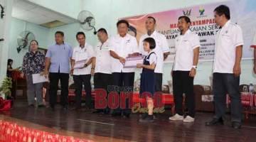 TERIMALAH: Mawan menyampaikan Baucar Bantuan Pakaian Seragam kepada murud pada majlis penyampaian di Dewan Masyarakat Pakan pada 15 November lalu.