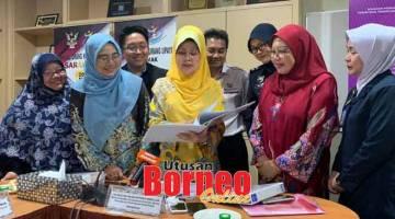MAKLUMAT: Fatimah meneliti dokumen sambil disaksikan wakil-wakil daripada agensi lain selepas mempengerusikan mesyuarat OSTPC di Kuching, semalam.