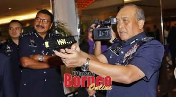 CUBA: Rosli mencuba pistol di salah sebuah gerai pameran yang dilawatinya pada Majlis Penutupan Persidangan Tahunan Persatuan Polis Bantuan Malaysia Ke-13 di Kuching, semalam.