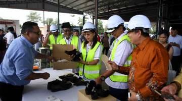 TINGKAT EKONOMI: Teresa Kok (tengah) melihat kasut yang dihasilkan daripada pokok kenaf ketika merasmikan Pusat Industri Kenaf di Kampung Tebu Hitam semalam. — Gambar Bernama
