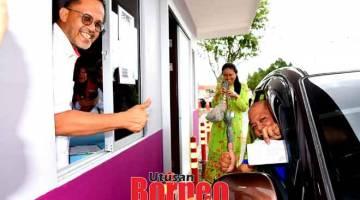 KETERUBAH: Dr Ramli (kiba) lebuh ti nyuaka ubat ngagai Roslan ti nyadi orang keterubah ngena servis 'Farmasi Pandu Lalu' ba Sepital Sibu.