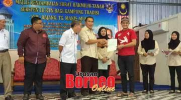 UNTUK RAKYAT: Len (empat kiri) menyerahkan surat hak milik kepada salah seorang penerima surat hak milik tanah Seksyen 18 Kanun Tanah Negeri bagi Kampung Rajang, Tanjung Manis, semalam.