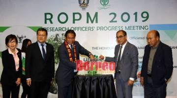Dr Rahman ngetas tali riben bup 'Panduan Bergambar Perosak Buah-buahan di Sarawak' kelai bejadika bup nya,  seraya diperatika Dr Alvin (dua kiba),  seharitu. - Gambar Muhammad Rais Sanusi