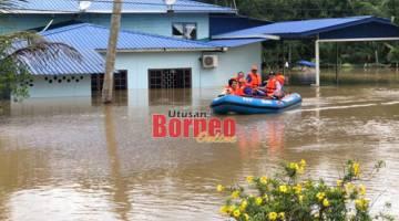 Anggota Angkatan Pertahanan Awam Malaysia memindahkan mangsa banjir