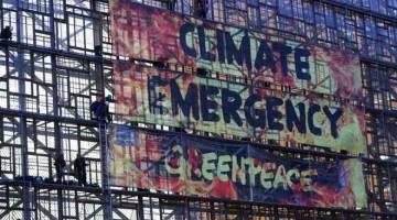 PROTES: Aktivis Greenpeace mempamerkan kain rentang di luar Ibu Pejabat Majlis Kesatuan Eropah menjelang persidangan pemimpin Kesatuan Eropah di Brussels, Belgium semalam. — Gambar Yves Herman/Reuters