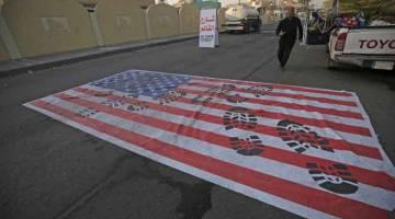 PROTES: Bendera olok-olok AS dibentangkan di atas jalan raya di Baghdad, Iraq semalam ekoran kematian komander tertinggi Iran dalam serangan AS ke atas konvoinya di Lapangan Terbang Antarabangsa Baghdad. — Gambar Ahmad Al-Rubaye/AFP