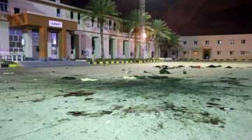 SERANGAN MAUT: Kesan bedilan daripada jet pejuang dapat dilihat meretakkan konkrit di pekarangan maktab tentera di wilayah Al-Hadaba di Tripoli, kelmarin. — Gambar AFP