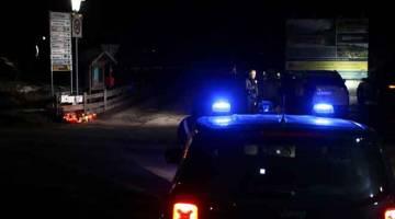 TRAGIK: Seorang wartawan membuat liputan berdekatan kereta 'carabinieri' Itali dengan lilin dan jambangan bunga diletakkan di tempat kejadian di Via Aurina SS 621, Lutago, Tyrol Selatan kelmarin. — Gambar AFP