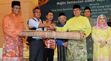 PENGHARGAAN: Abang Johari menerima 'kasah' daripada Ketua Gawai juga wakil SEB, Sipol Ambun (dua kiri) sebagai simbolik berakhirnya sambutan Gawai pada Majlis Gawai Raya SEB pada Jun 2019.