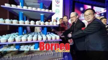 ULANG TAHUN KELIMA: (dari dua kanan) Wan Hamid, Fattah dan Gan bersama-sama yang lain memotong kek sempena ulang tahun kelima KOPBARIS.